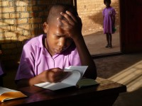 A student studies in the early morning sunlight at Emmanuel Christian School in Nsaalu, Uganda, where they lack electricity and running water.