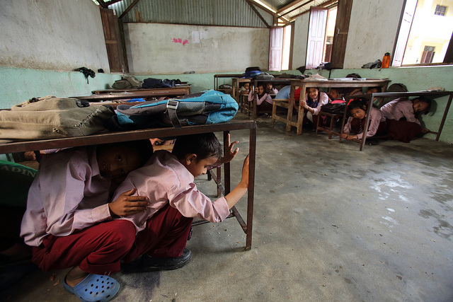 Students practice earthquake drill at Jana Bikash Secondary School, in Matatirtha, Kathmandu District, is in the process of being redeveloped to make the school more earthquake proof. As part of this process children are taught how to take shelter beneath their desks in case of an earthquake. Photo by Jim Holmes for AusAID. Creative Commons License.