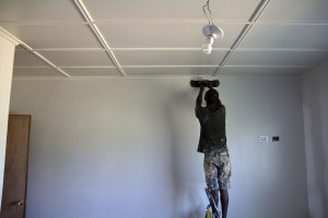 Our worker (Emmanuel) paints the ceiling trim in one of the four bedrooms where the temporary light sockets were recently installed.