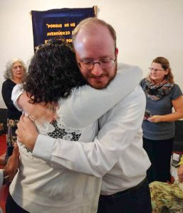 Rev Jason Boyle hugs one of the members of his congregation after his ordination service.