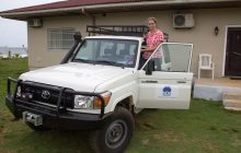 Missionary Joanne Greer standing the running board of the new Toyota Land Cruiser.