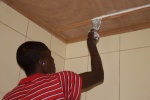 Emmanuel, a mission compound worker, applies putty to the ceiling in one of the three bathrooms.jpg