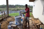 Emmanuel, one of the mission compound employees, prepares to clean rust and ocean salt off the window bars.jpg